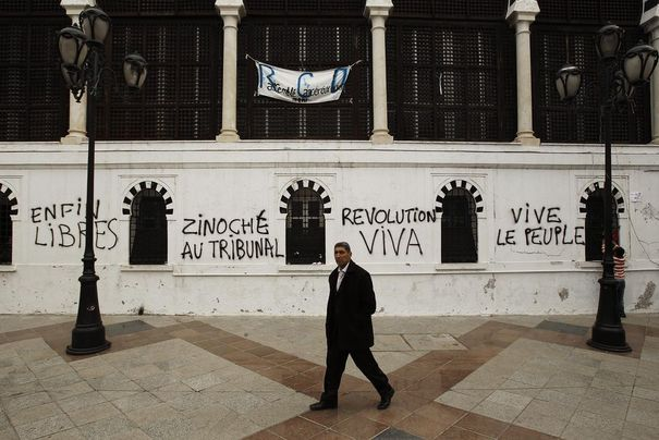 789868_a-man-walks-past-recent-graffiti-on-the-prime-ministers-office-walls-in-tunis