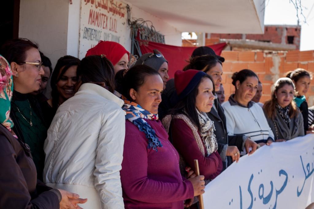 Le operaie all'entrata della fabbrica Mamotex, rivendicano con uno striscione il loro diritto al lavoro. Crédit image: Monia Ben Hamadi per Inkyfada