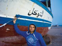 Patrick Zachmann // M. Ali Ghommidh, 19 ans, pose devant le bateau sur lequel il a embarqué, avec cent autres migrants clandestins, en direction de l'Europe. Le chalutier a failli sombrer, et ses passagers ont été sauvés par la marine tunisienne, Zarzis, avril 2011 Magnum Photos