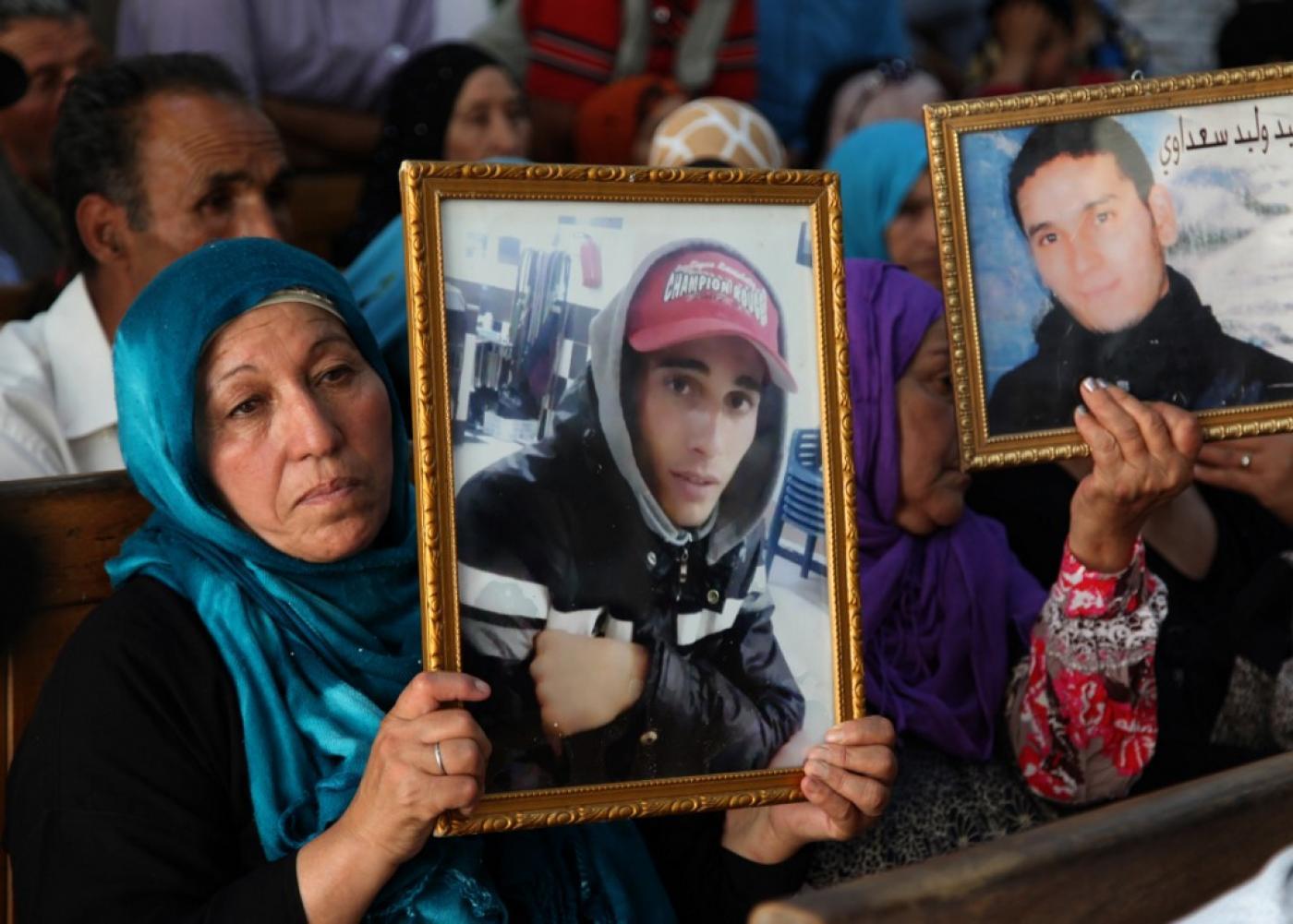 Des familles de victimes de la révolution tunisienne montrent des photos de leurs proches à l'intérieur du palais de justice de Kasserine lors d'un procès organisé par l'Instance vérité et dignité, le 13 juillet 2018 (AFP)